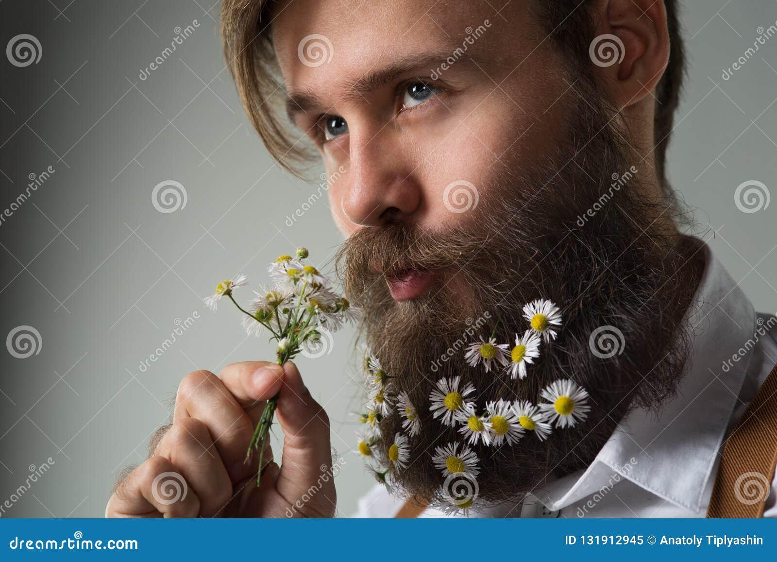 Mężczyzna z stokrotką kwitnie dekorującą brodę w białej koszula i suspen