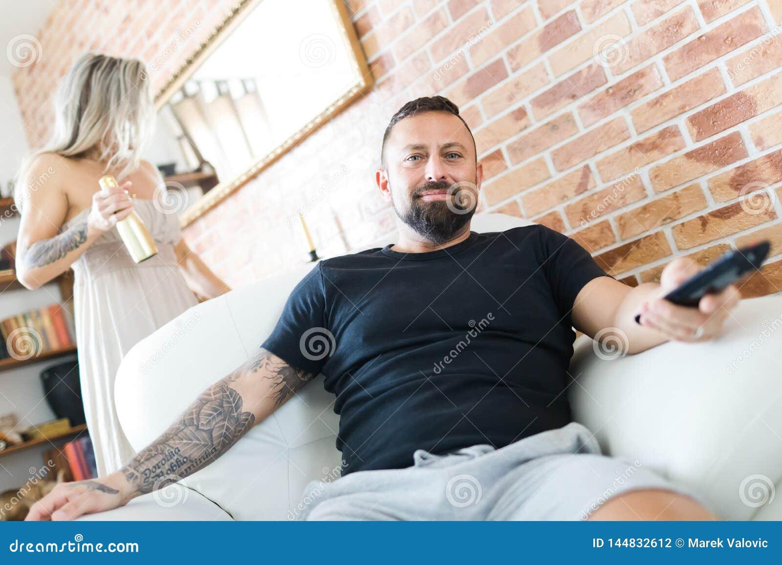 Mężczyzna z tatuażu dopatrywania telewizyjnym obsiadaniem w karle - kobieta jest przyglądająca w lustro