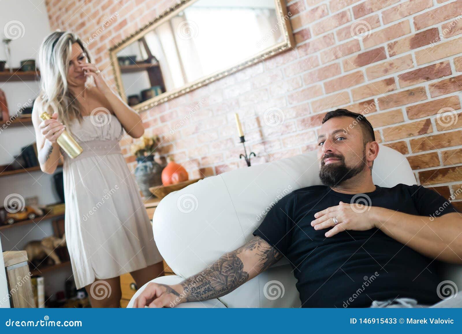 Mężczyzna z tatuażu obsiadaniem w karle i kobiecie ma złotą butelkę szampan w tle