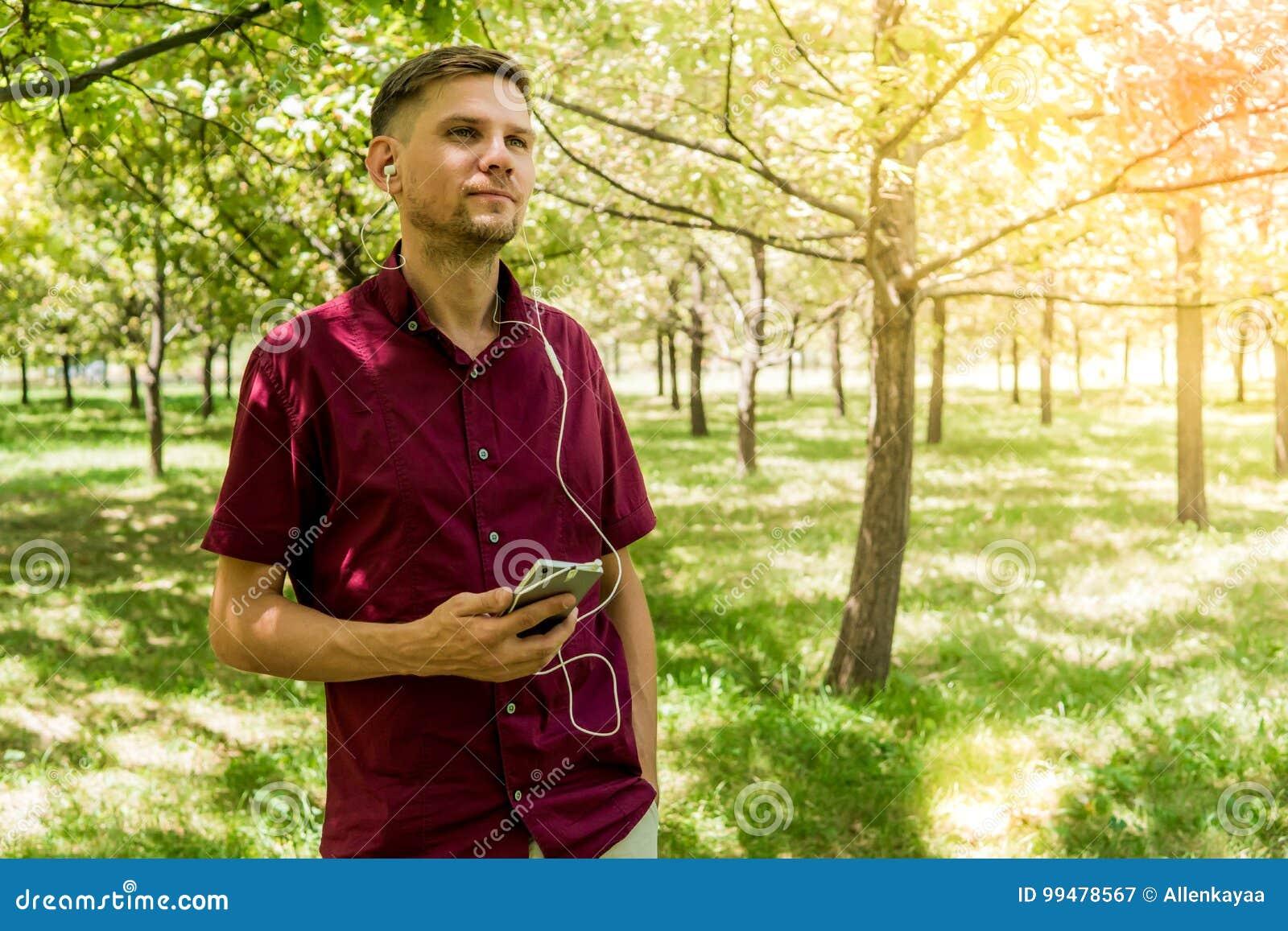 Mężczyzna z telefonem komórkowym w lato parku Młody przystojny mężczyzna z sm