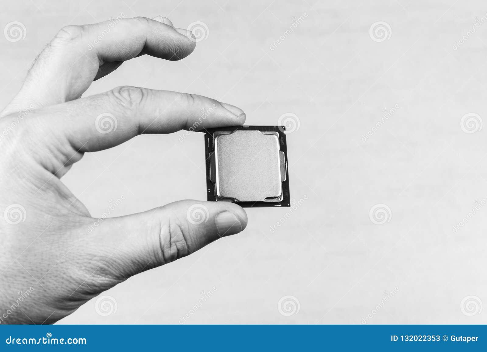 Mężczyzny mienia palce wyśmiewają w górę desktop procesoru 8th gen na popielatego tła zbliżenia odgórnym widoku