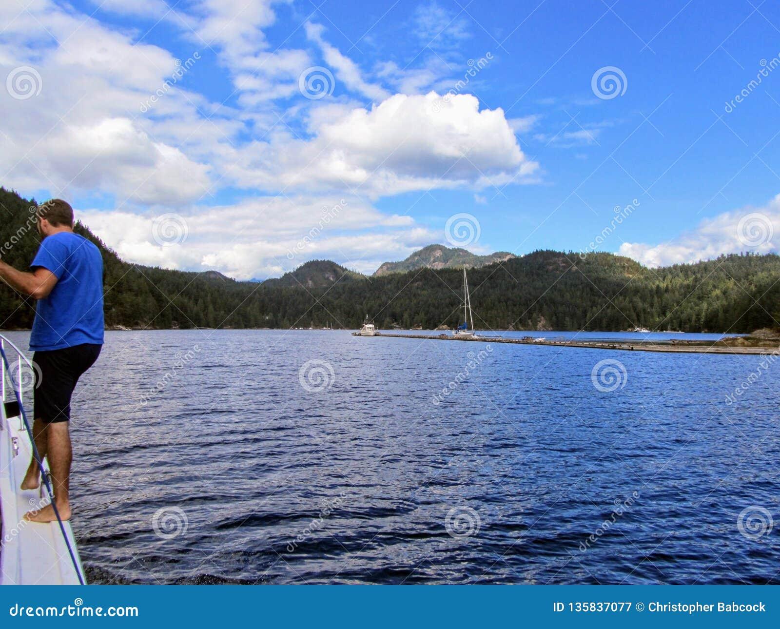 Mężczyzny narządzanie dokować jego łódź przy dokiem na Aleksander wyspie na gambir wyspie w Howe dźwięku, kolumbia brytyjska, Kan