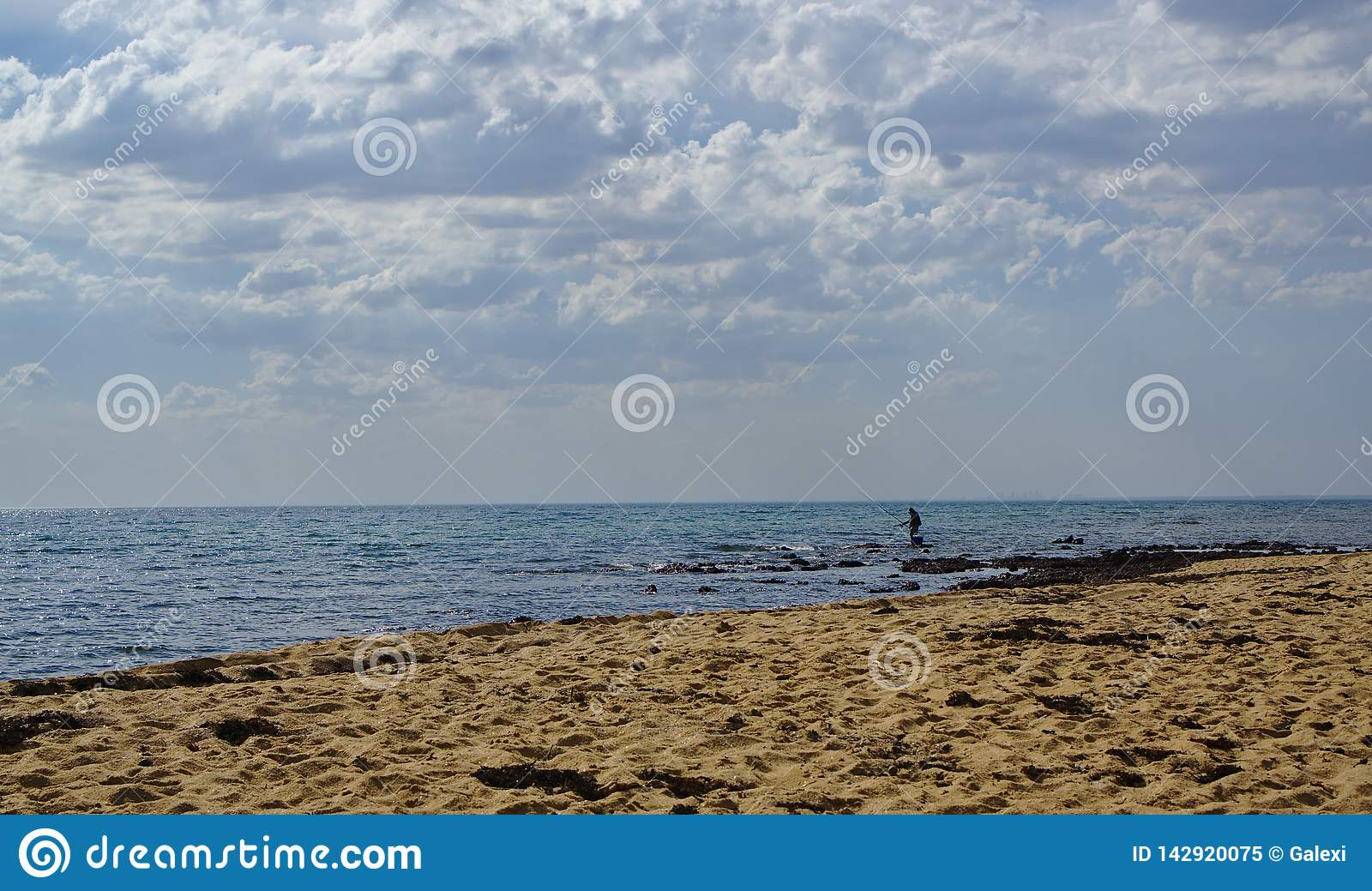 Mężczyzny połów w błękitne wody na chmurnym dniu