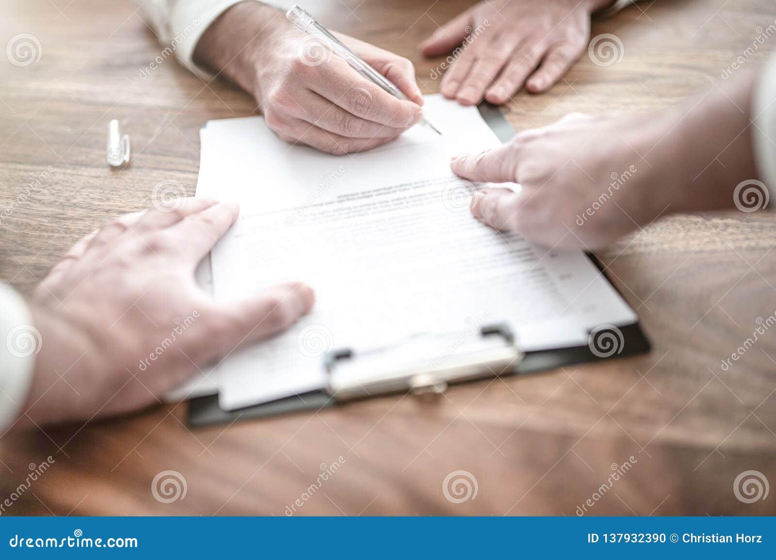 Mężczyzny podpisywania kontrakt przy drewnianym biurkiem z inną osobą wskazuje przy dokumentem