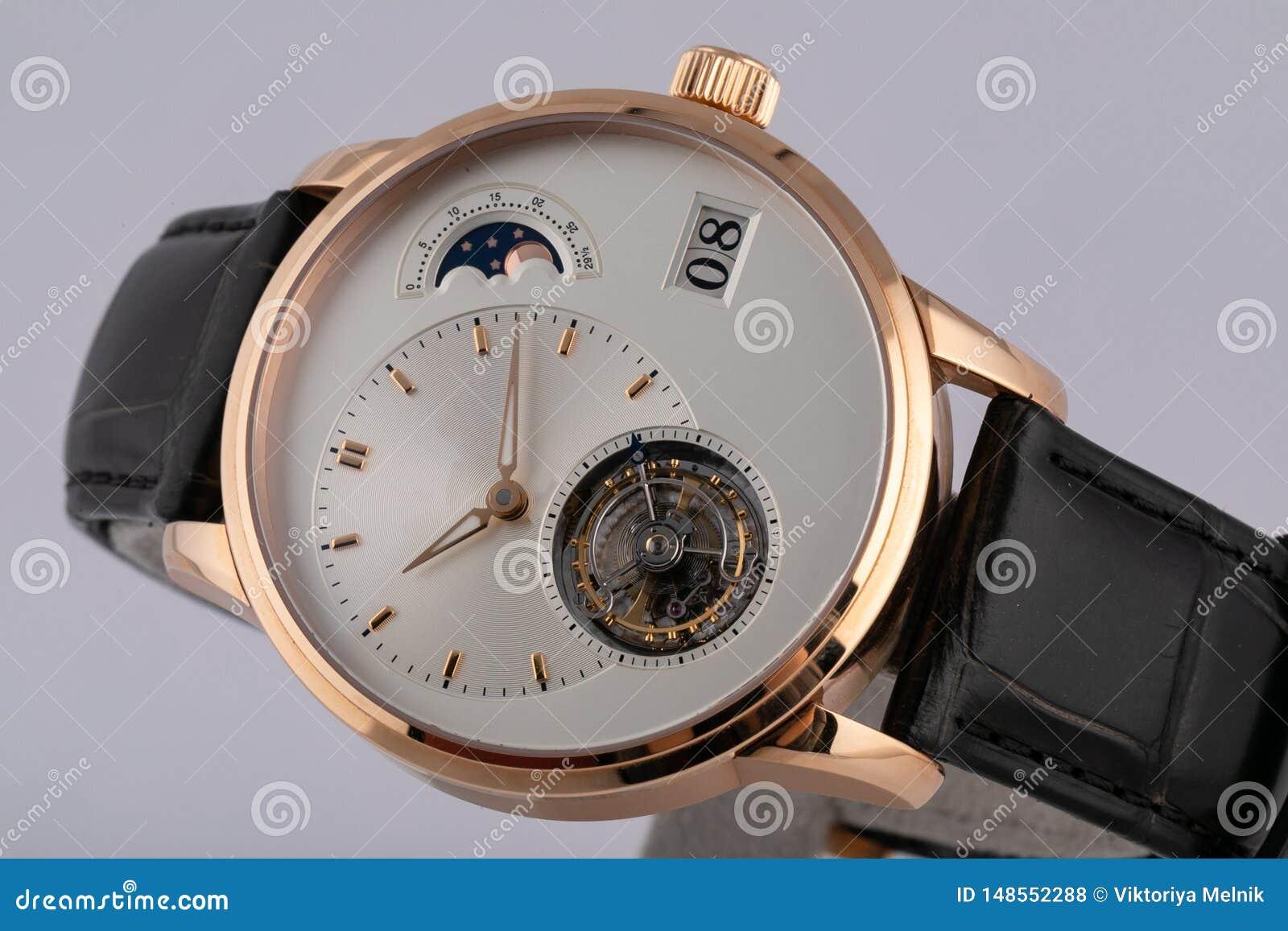 Mężczyzny złocisty zegarek z białą tarczą, złoty clockwise chronografu stopwatch z czarną rzemienną patką odizolowywającą na biał