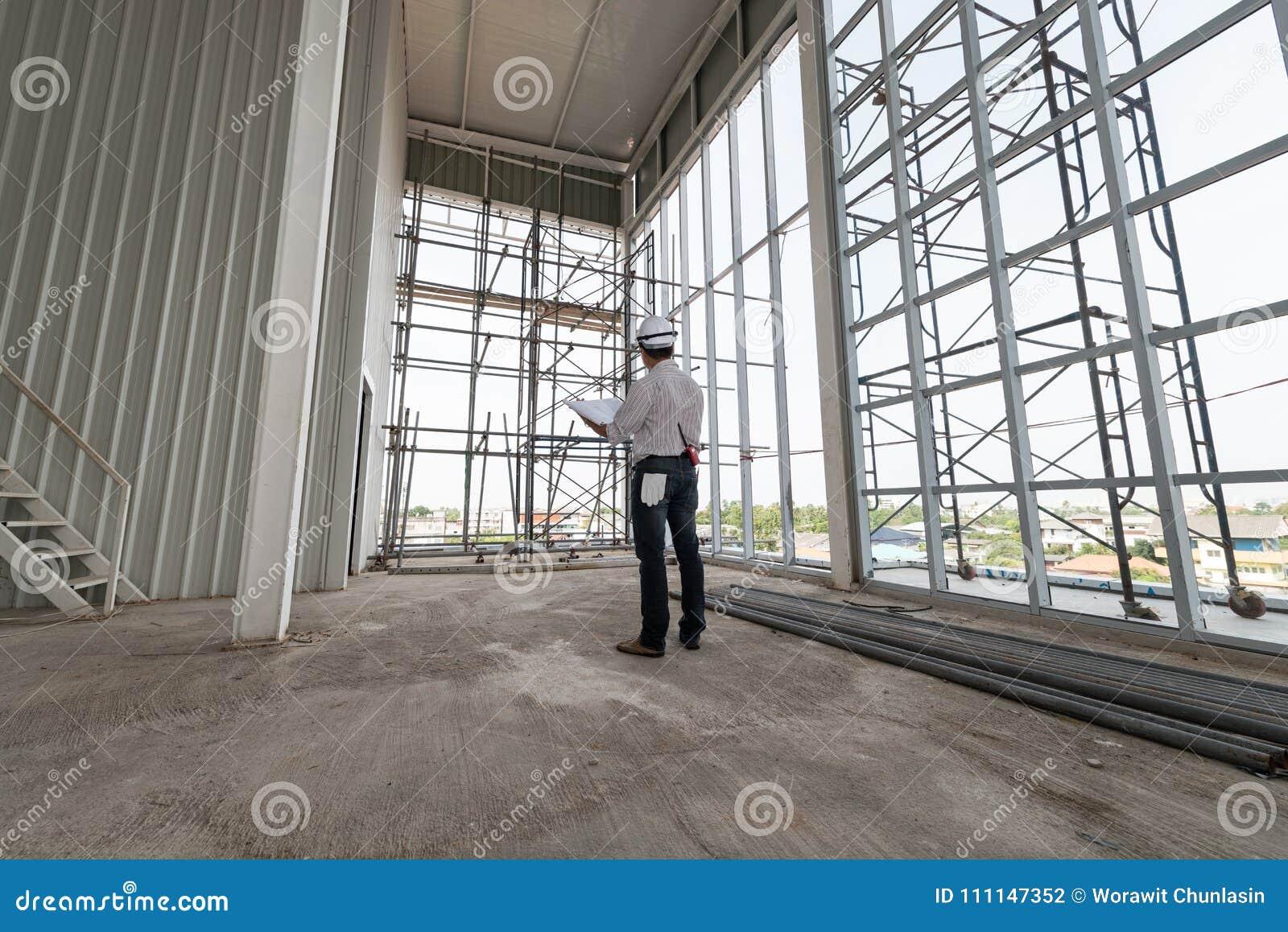Męscy inżyniery stoją zegarka modela w budynek budowie