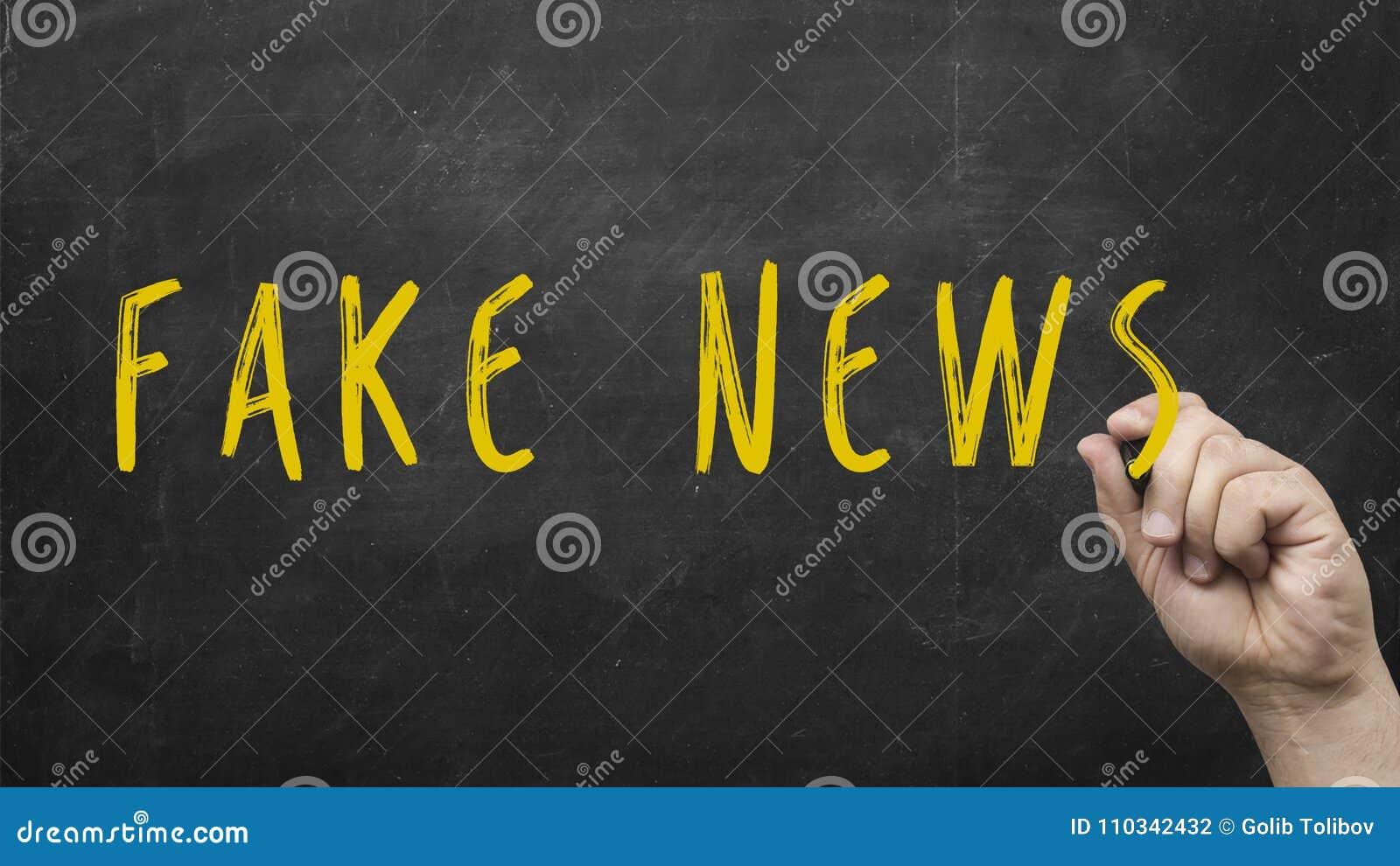 Męska ręka pisze słowom Sfałszowanej wiadomości na chalkboard jako przypomnienie być świadomy bajerowania i dezinformacja dla pro