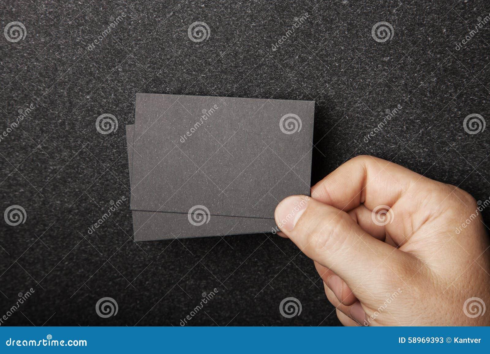 Męska ręka trzyma dwa czarnej wizytówki na