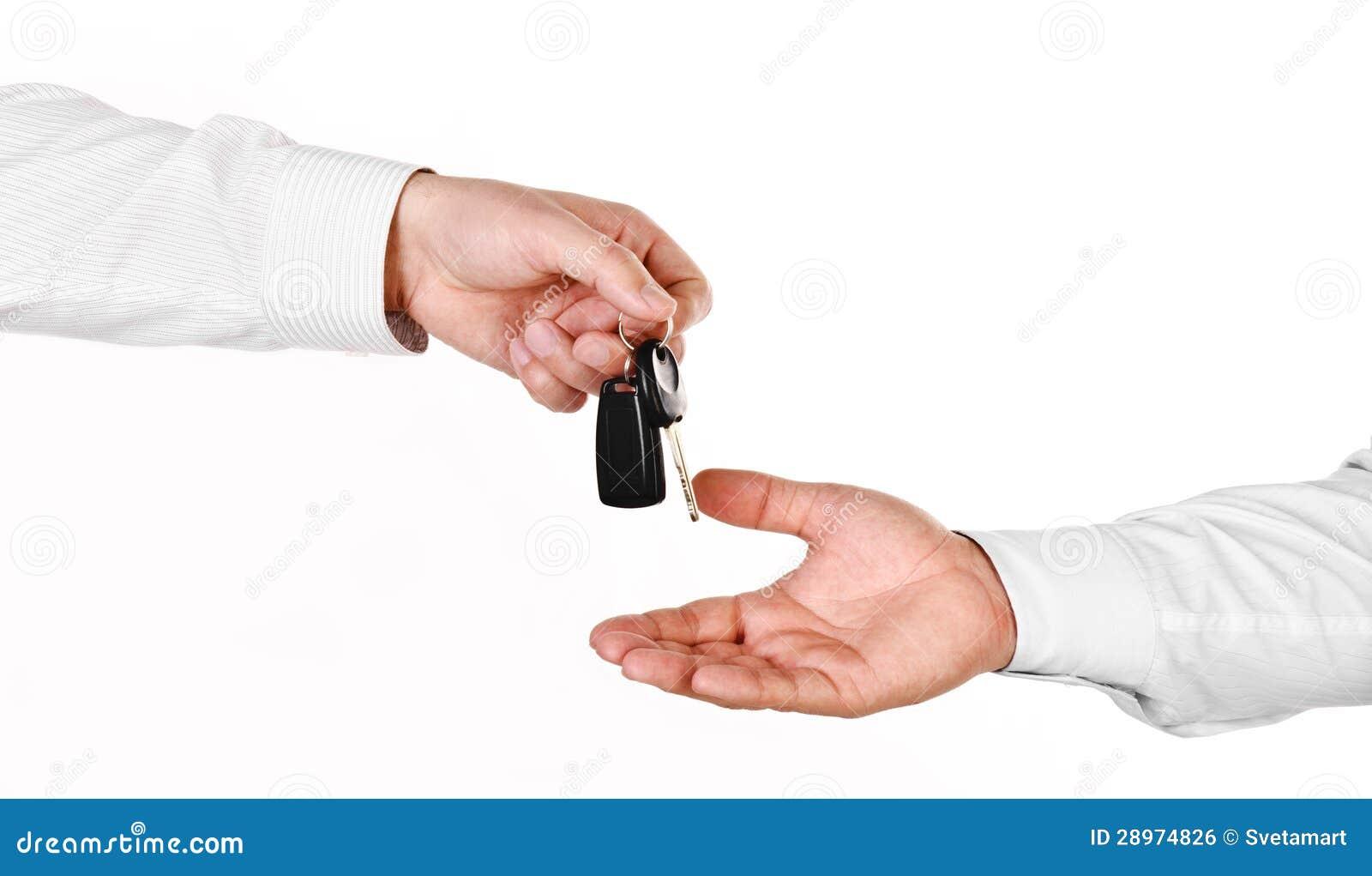 Męska ręka trzyma samochodowego klucz i wręcza je inny perso