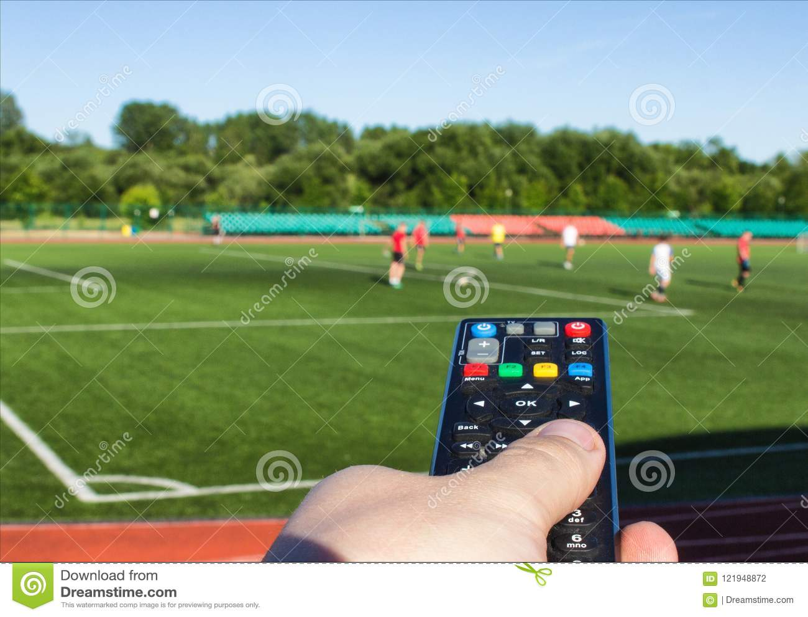 Męska ręka z pilot do tv od telewizoru przeciw tłu boisko piłkarskie na którym bawić się futbol