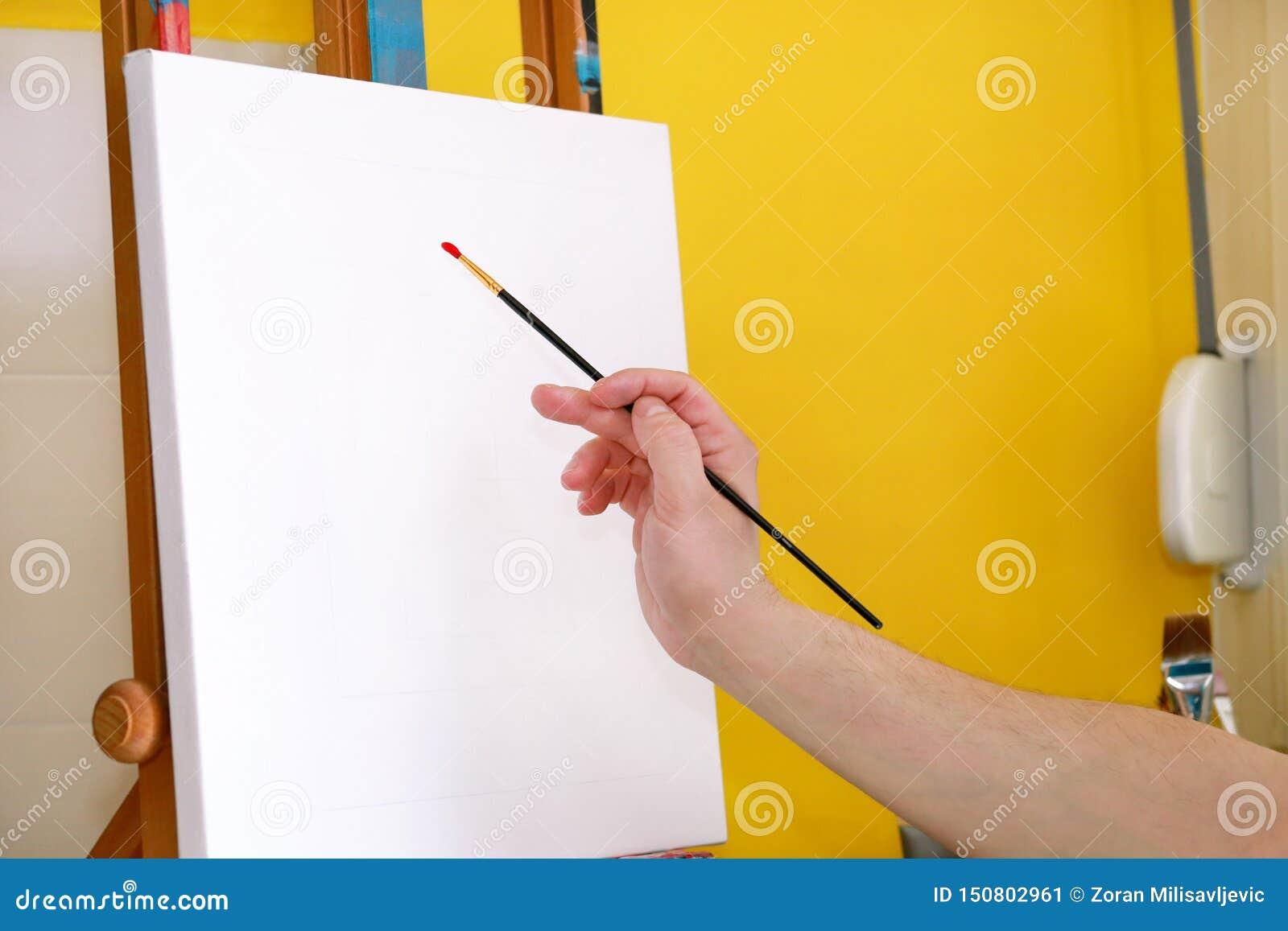 Męski artysty malarz pracuje w warsztacie z kanwą na drewnianej rysownicy sztaludze w sztuki farby studiu Portret artysta