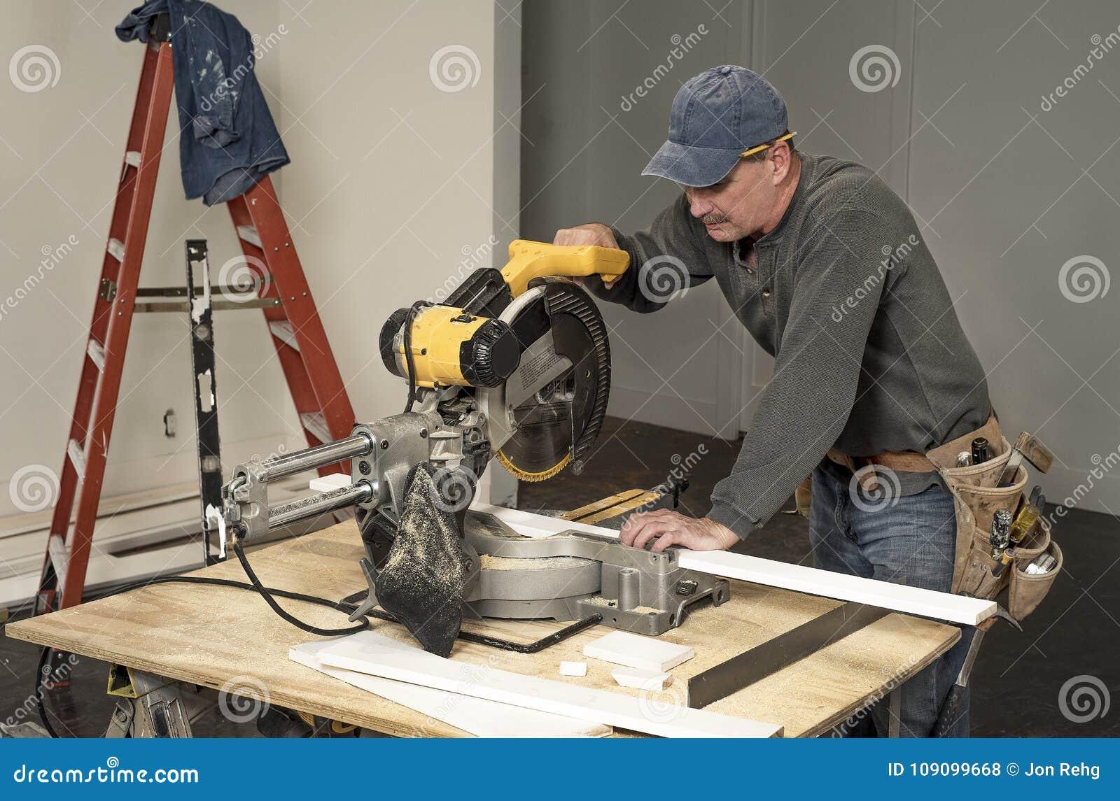 Męski cieśla jest ubranym narzędzia rozcięcia i paska drewna deskę z fachowym kotlecika saw na budowa domu przemodelowywa