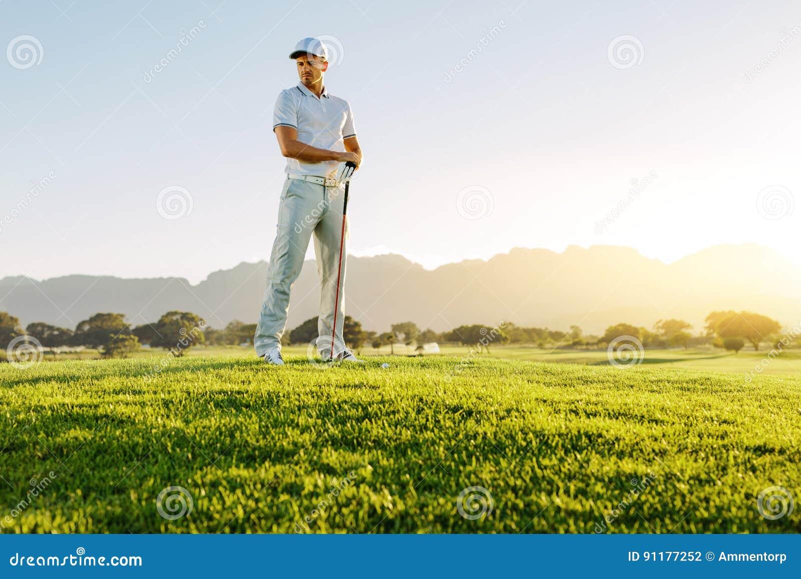 Męski golfista z kijem golfowym na śródpolny patrzeć daleko od