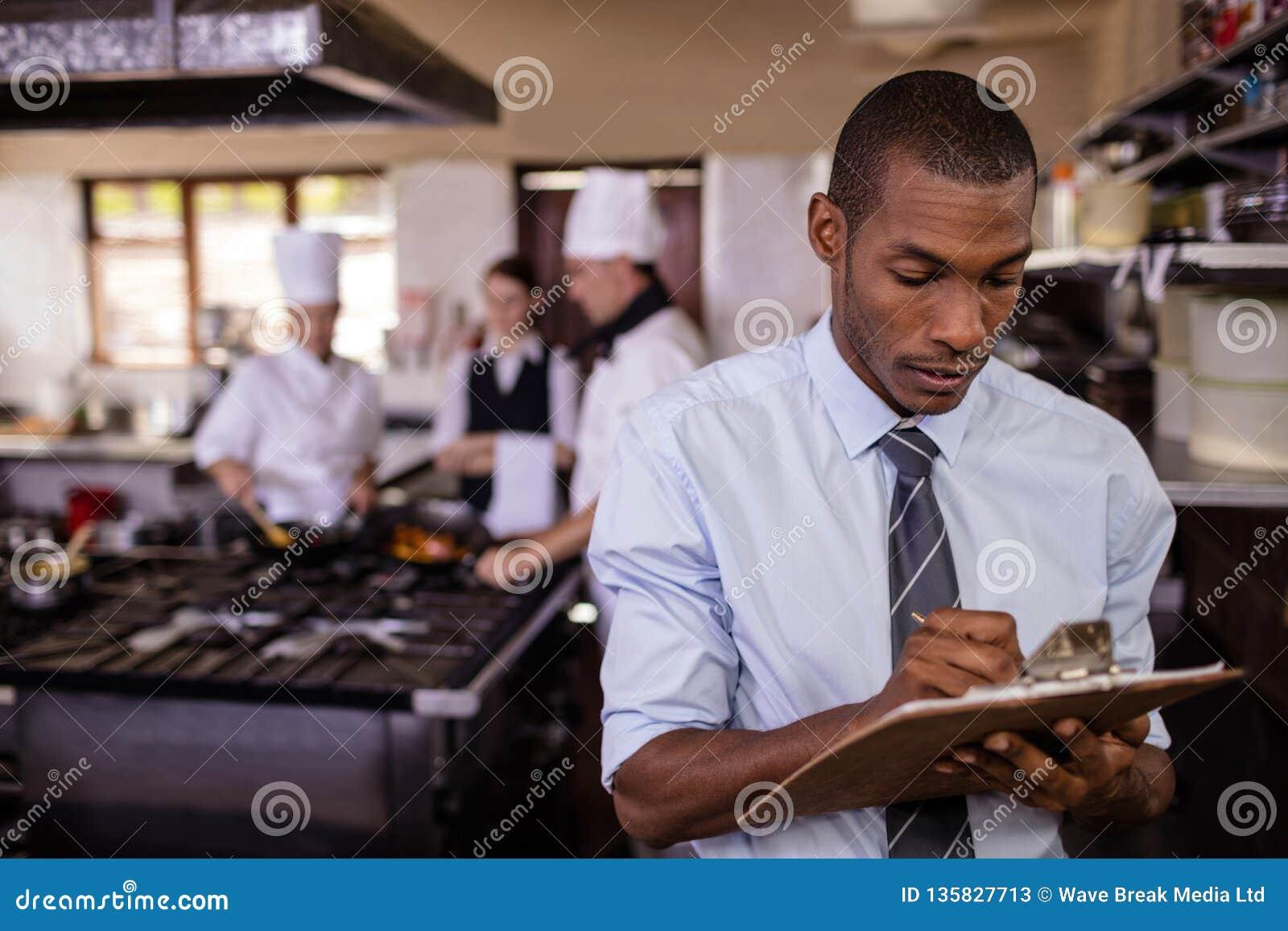 Męski kierownik pisze na clipbaord w kuchni