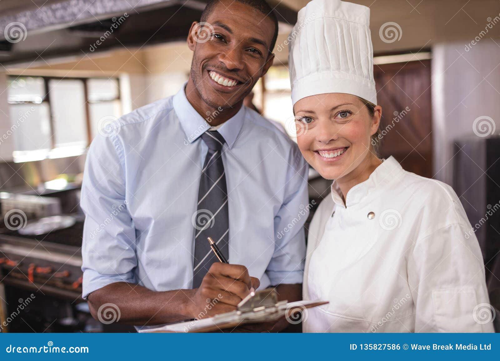 Męski kierownika i kobiety szef kuchni pisze na schowku w kuchni