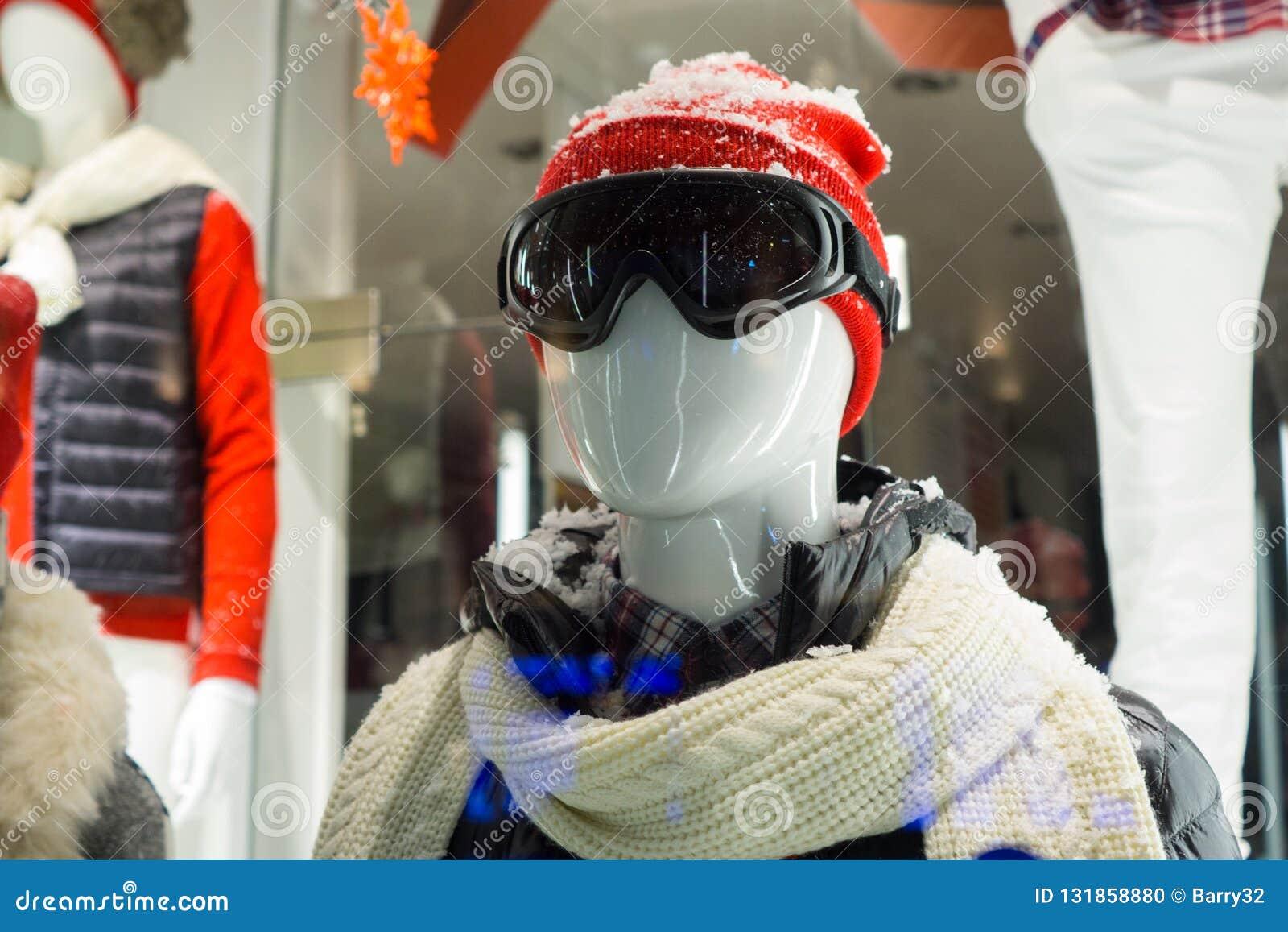 Męski mannequin w sklepu okno podczas zimy z narciarską przekładnią, zwełnionym kapeluszem, ciemnymi gogle, szalikiem, puszek kur