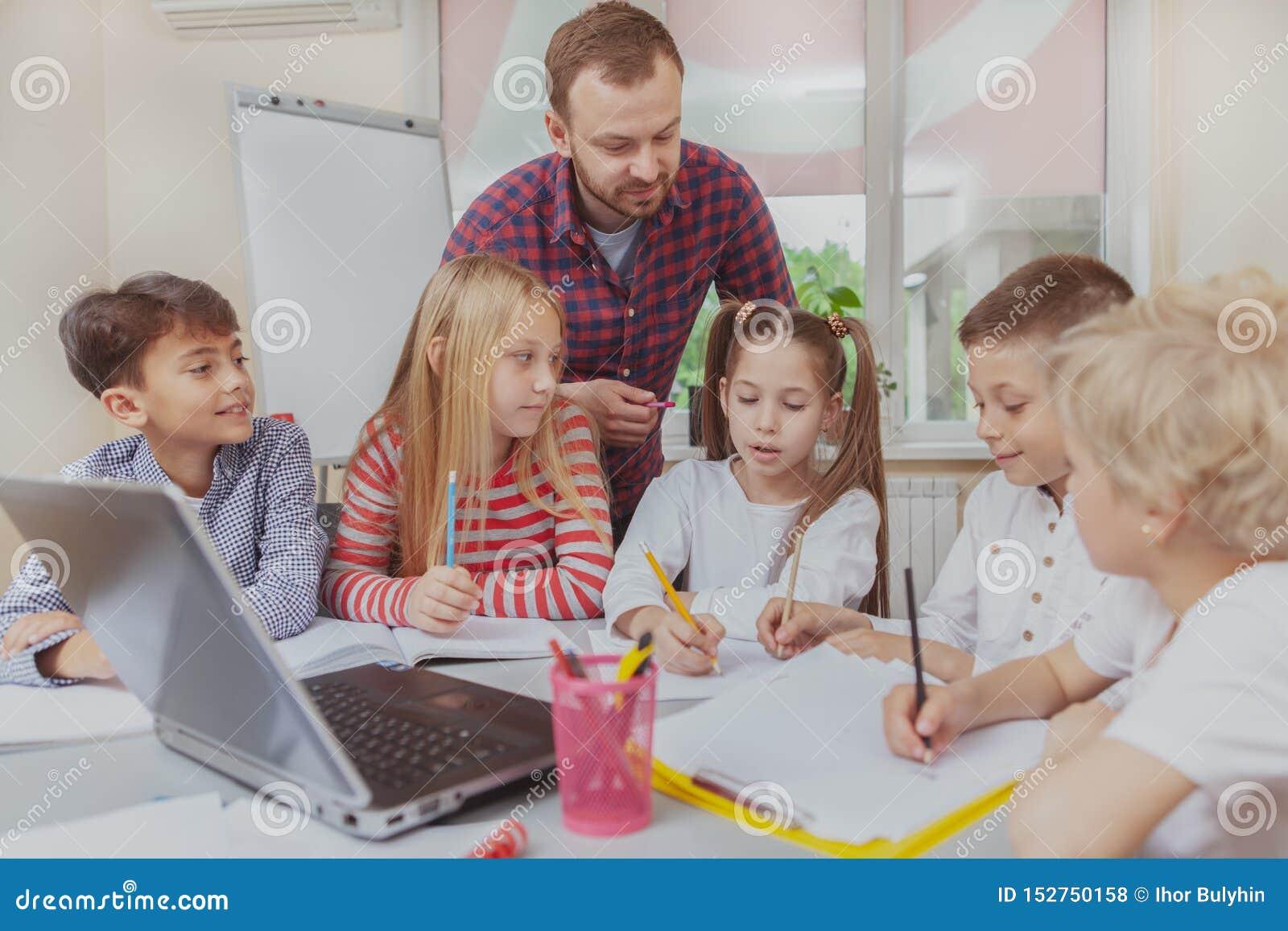 Męski nauczyciel pracuje z dziećmi przy preschool