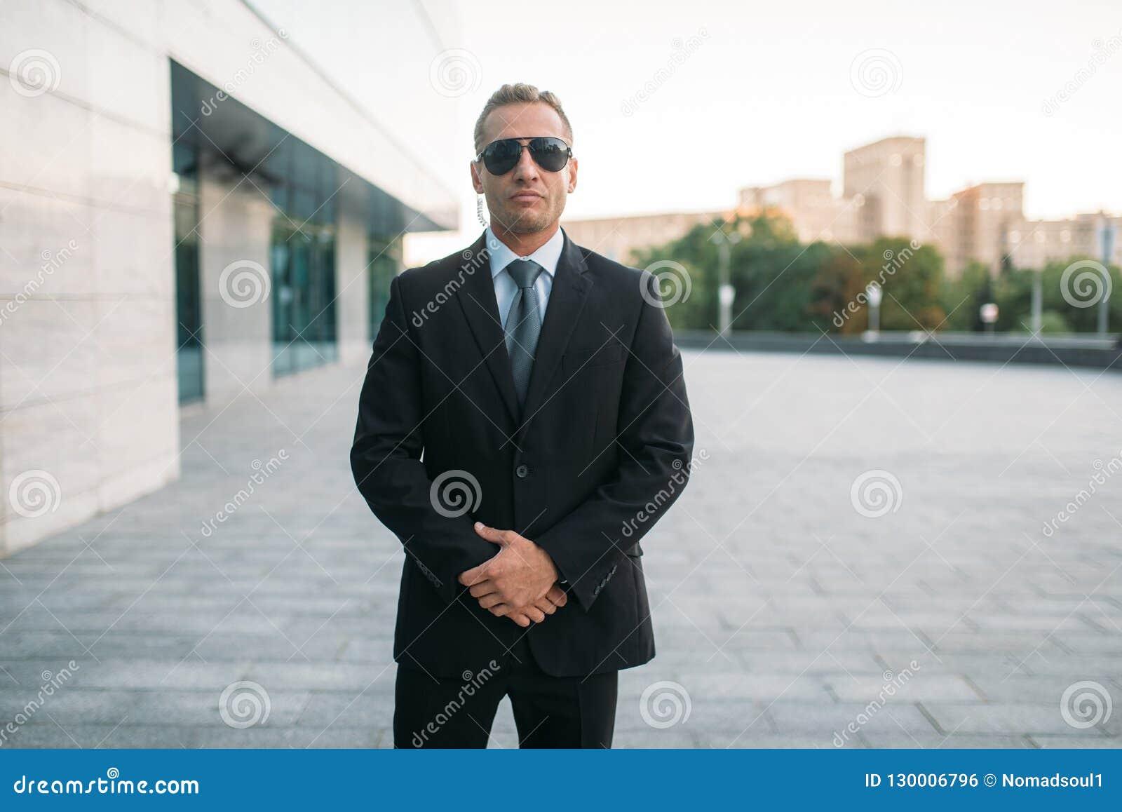 Męski ochroniarz w kostiumu, earpiece i okularach przeciwsłonecznych,