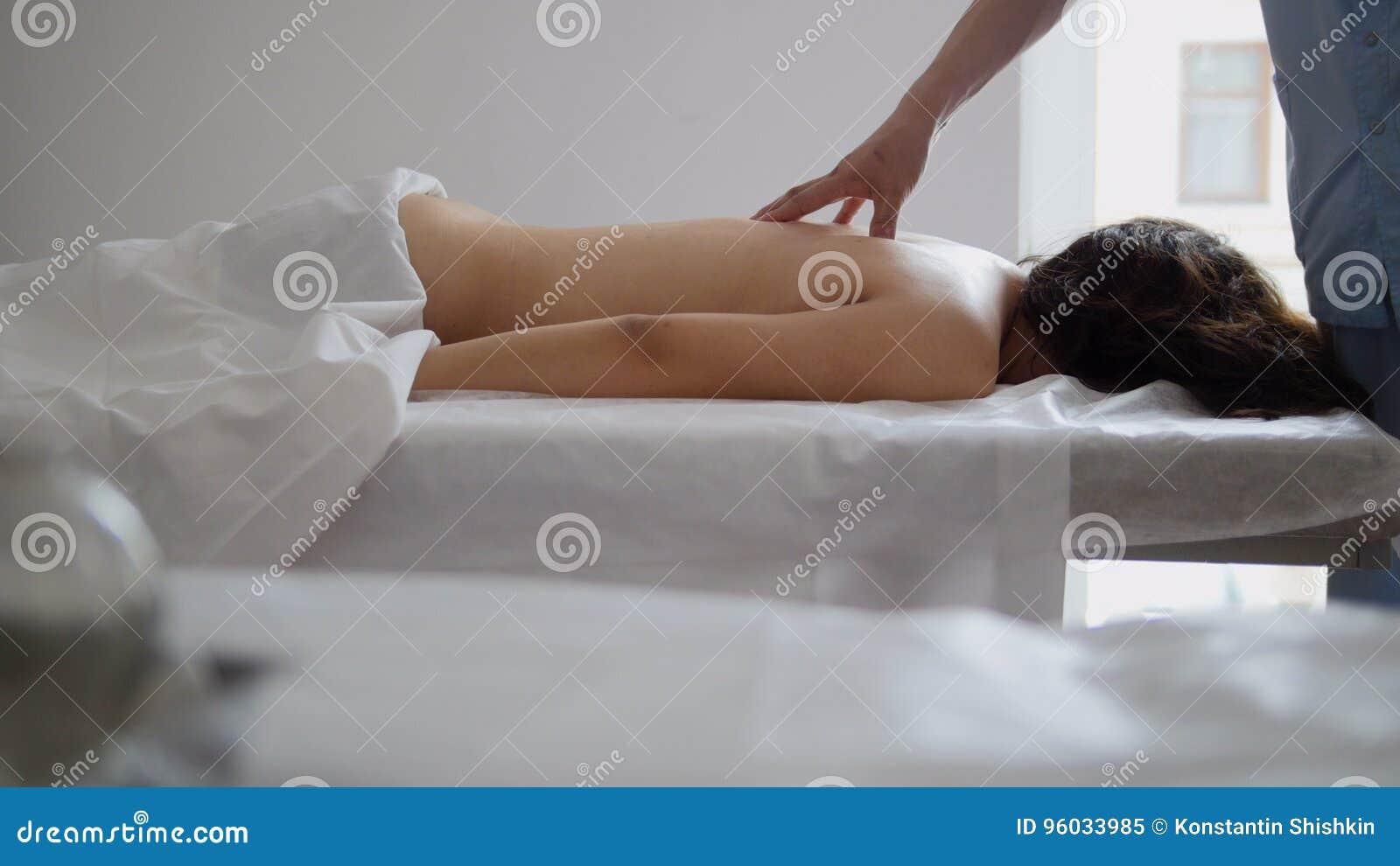Męski physiotherapist masowania kobiety ` s plecy w medycznym biurze