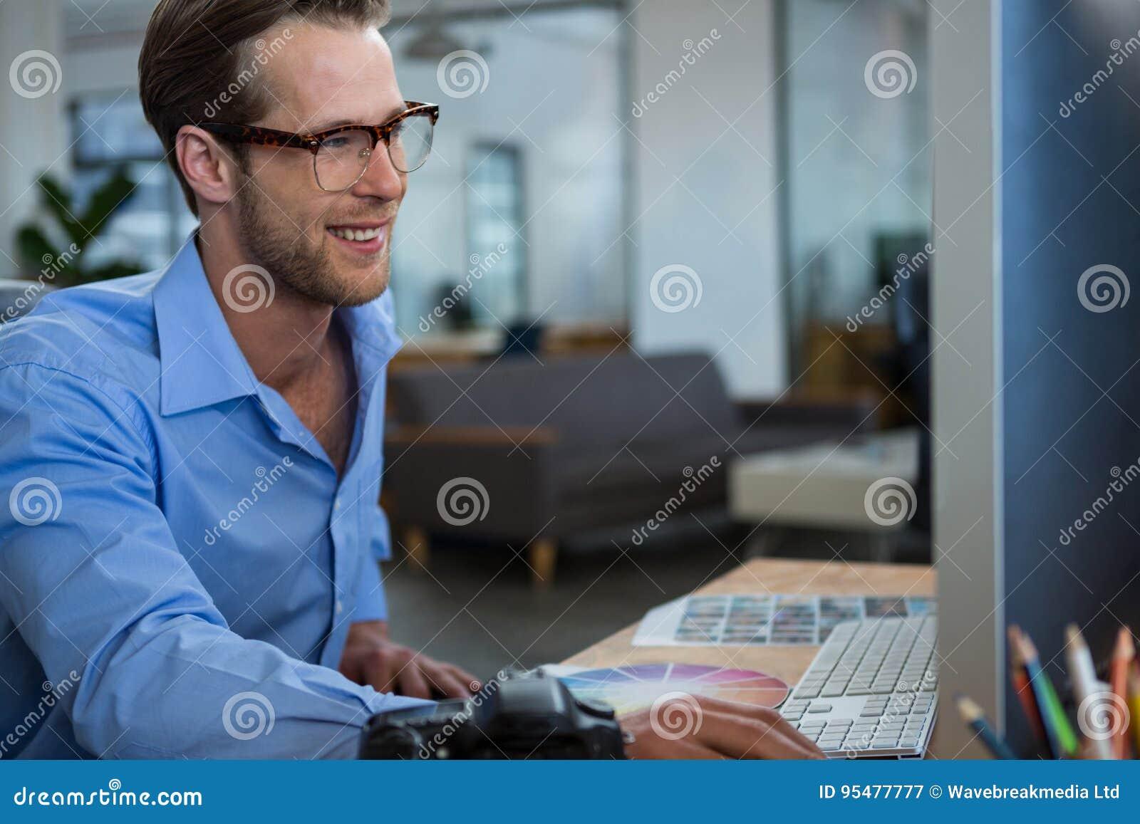 Męski projektant grafik komputerowych pracuje przy biurkiem