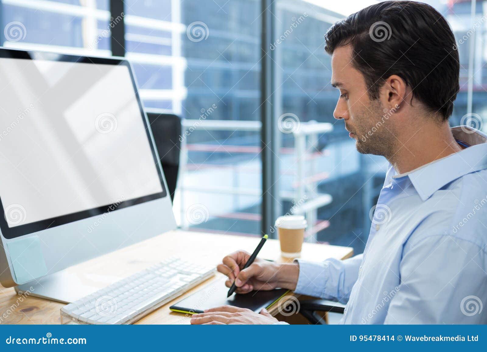 Męski projektant grafik komputerowych używa grafiki pastylkę przy biurkiem