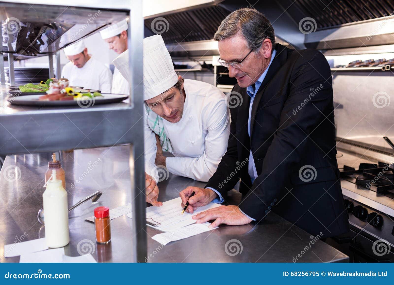 Męski restauracyjny kierownika writing na schowku podczas gdy oddziałający wzajemnie kierowniczy szef kuchni