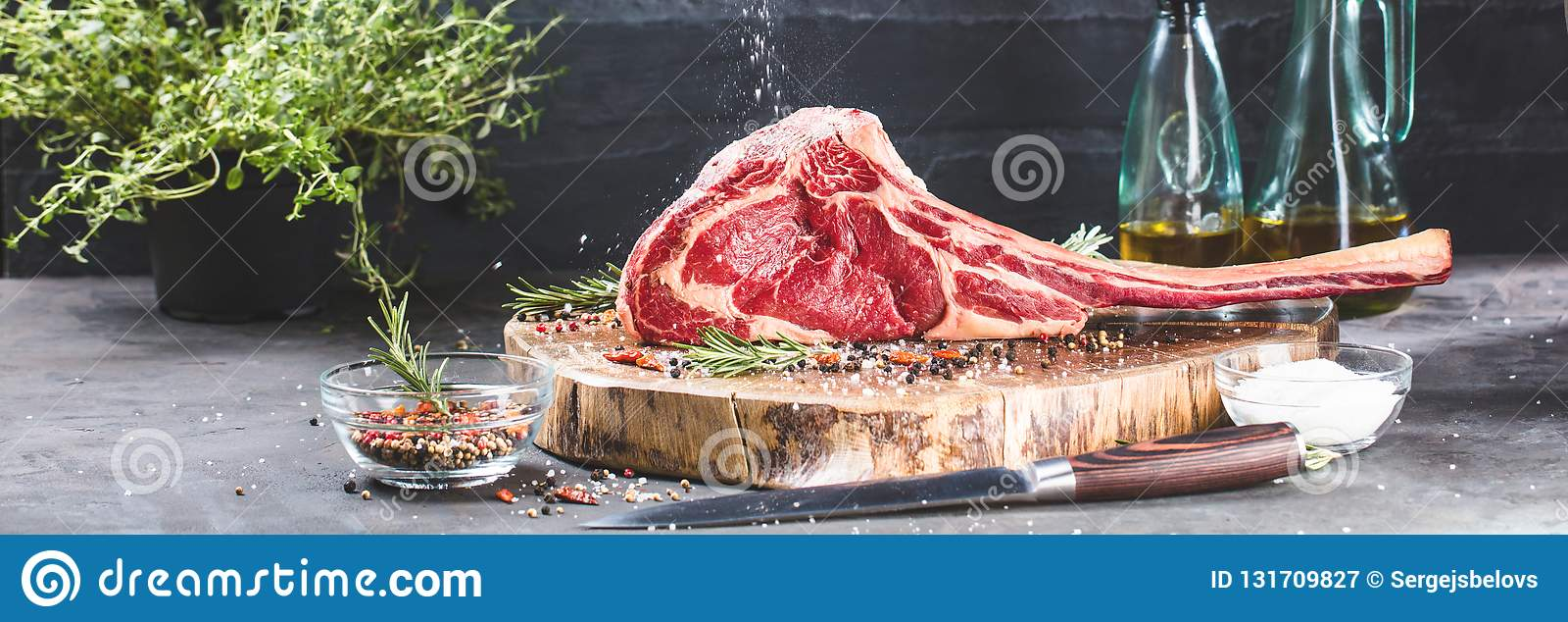 Męskie ręki masarki lub kucharza mienia tomahawka wołowiny stek na ciemnym nieociosanym kuchennego stołu tle
