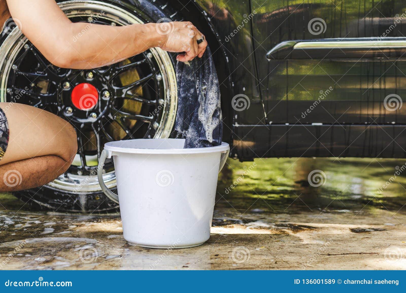 Męskie ręki z piankową tkaniną myje samochodowego koła Czyści koła Używają wodę