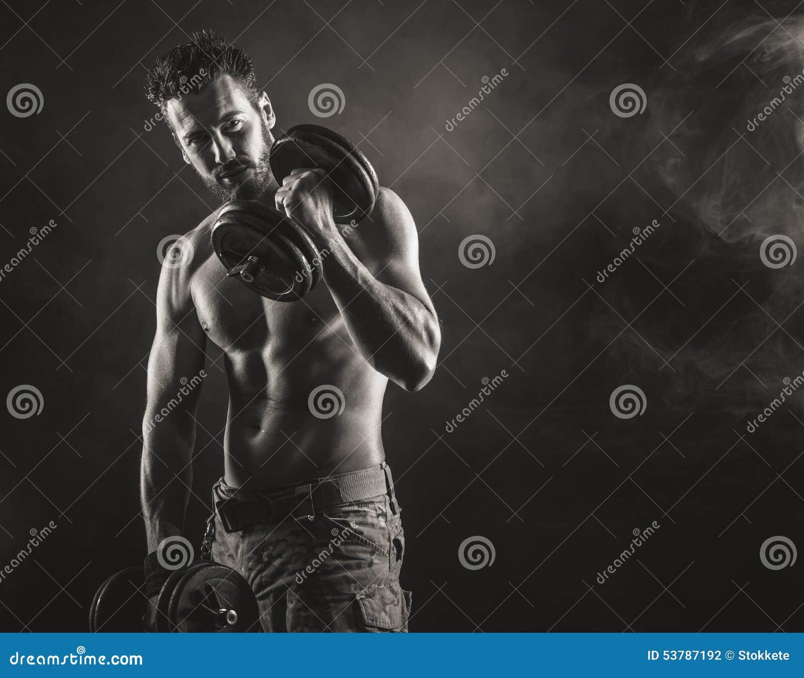Męskiego ciała budowniczy pracujący z dumbbells out