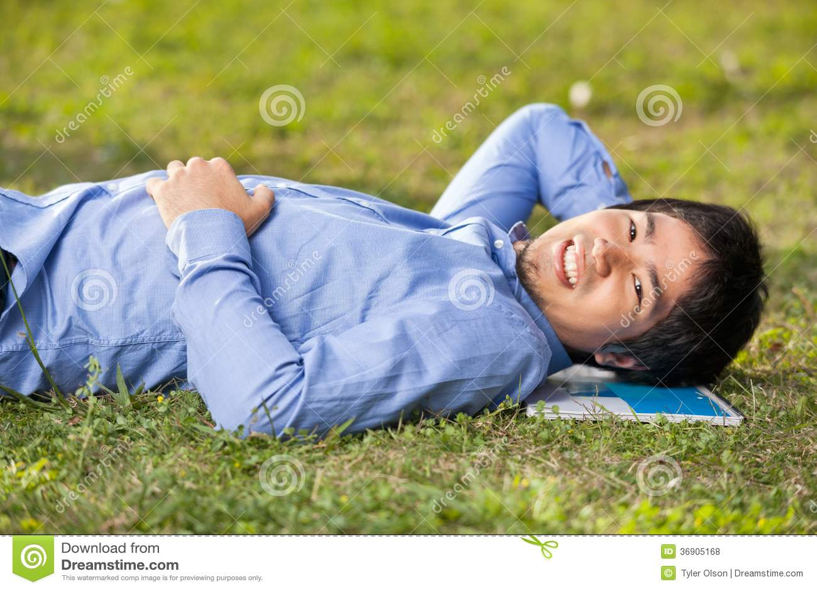 Męskiego ucznia lying on the beach Na trawie Przy szkoła wyższa kampusem