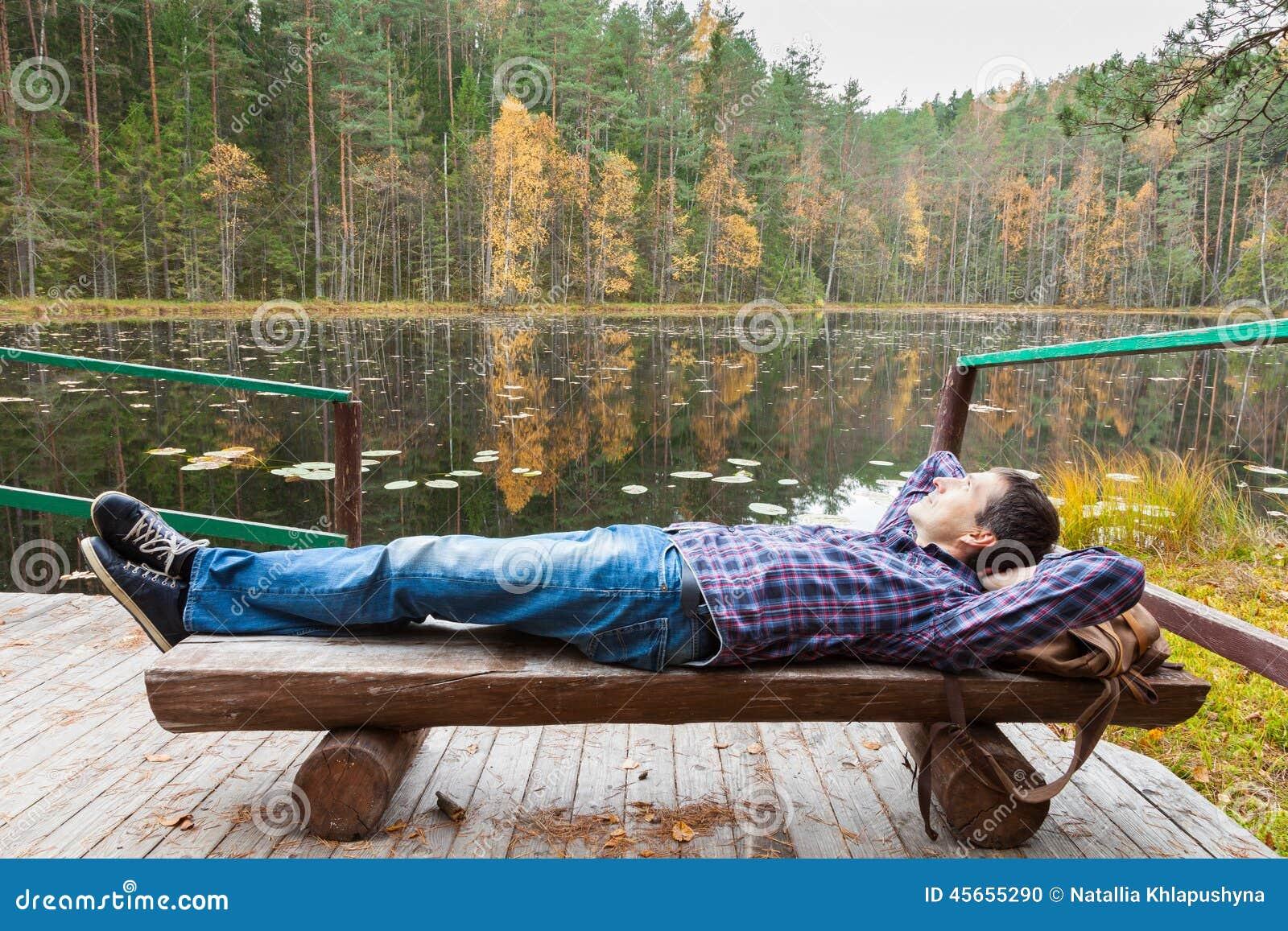 Męskiego wycieczkowicza odpoczynkowy pobliski jezioro w jesień lesie