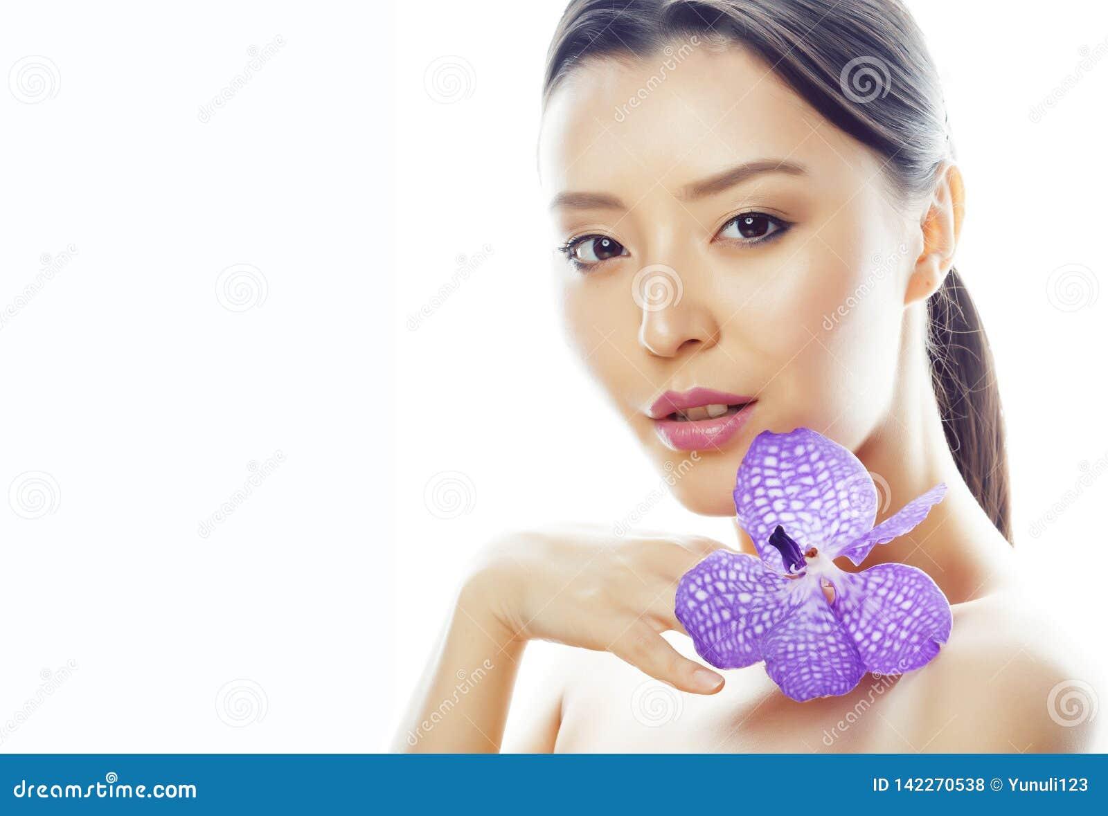 Młoda ładna azjatykcia kobieta z kwiat orchidei purpurowym zakończeniem up odizolowywał zdrój, kobieta dnia pojęcie