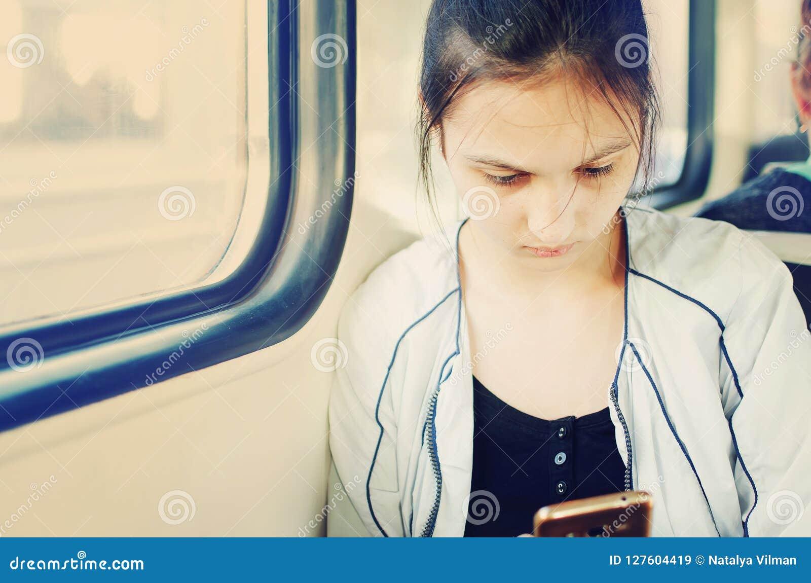 Młoda ładna dziewczyna iść taborowy samochód w smartphone spojrzenia i