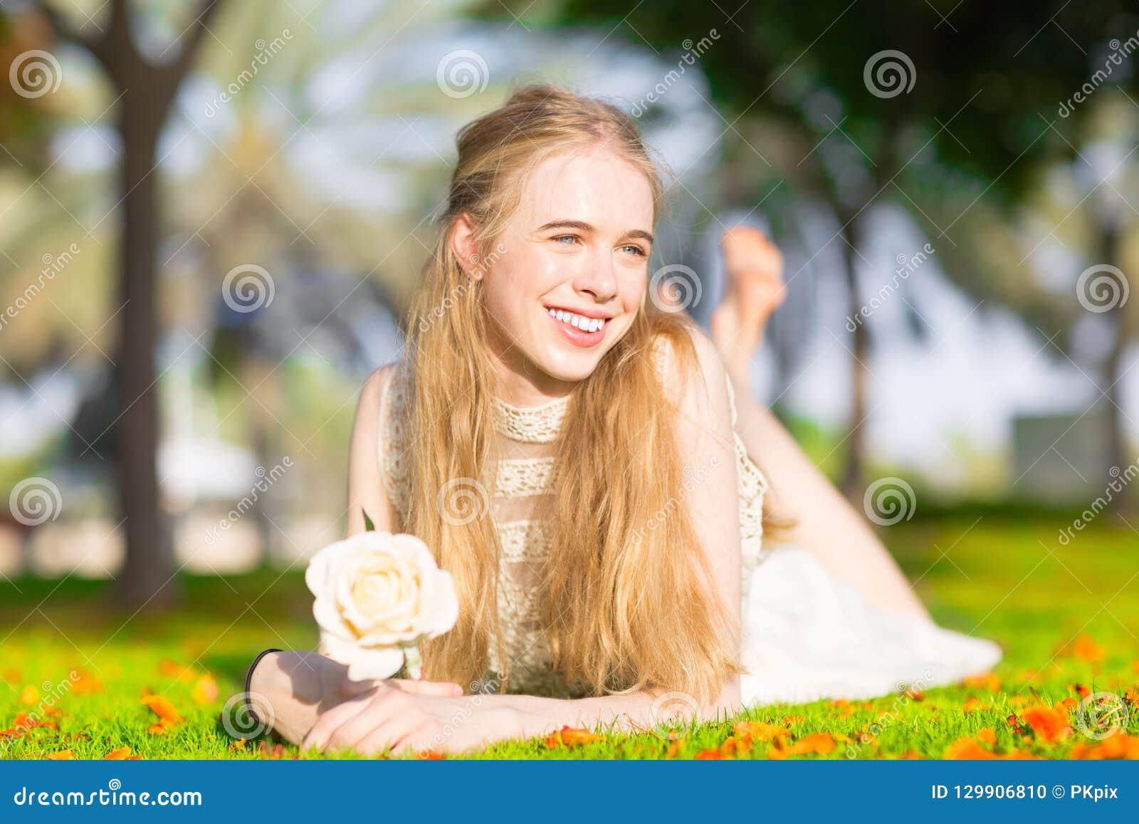 Młoda ładna dziewczyna trzyma białej róży w pogodnym parku