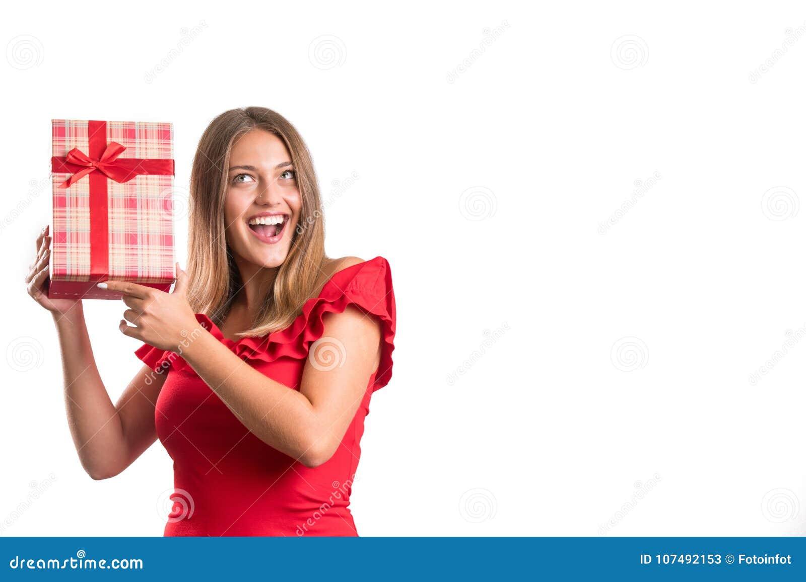 Młoda ładna dziewczyna w czerwieni sukni mienia teraźniejszość odosobniony