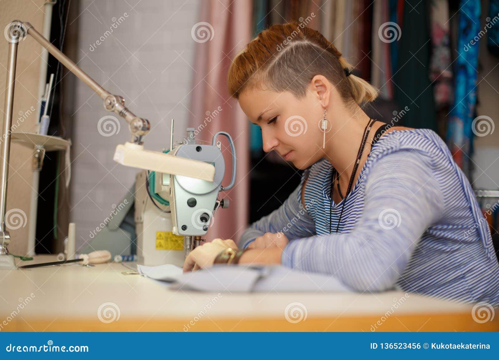 Młoda żeńska blondynki krawcowa pracuje na szwalnej maszynie smokingowy przemysł wytwórczy