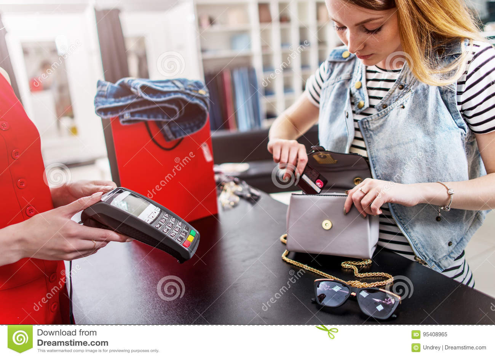 Młoda żeńska klient pozycja przy gotówkowym biurkiem płaci z kredytową kartą w odzież sklepie