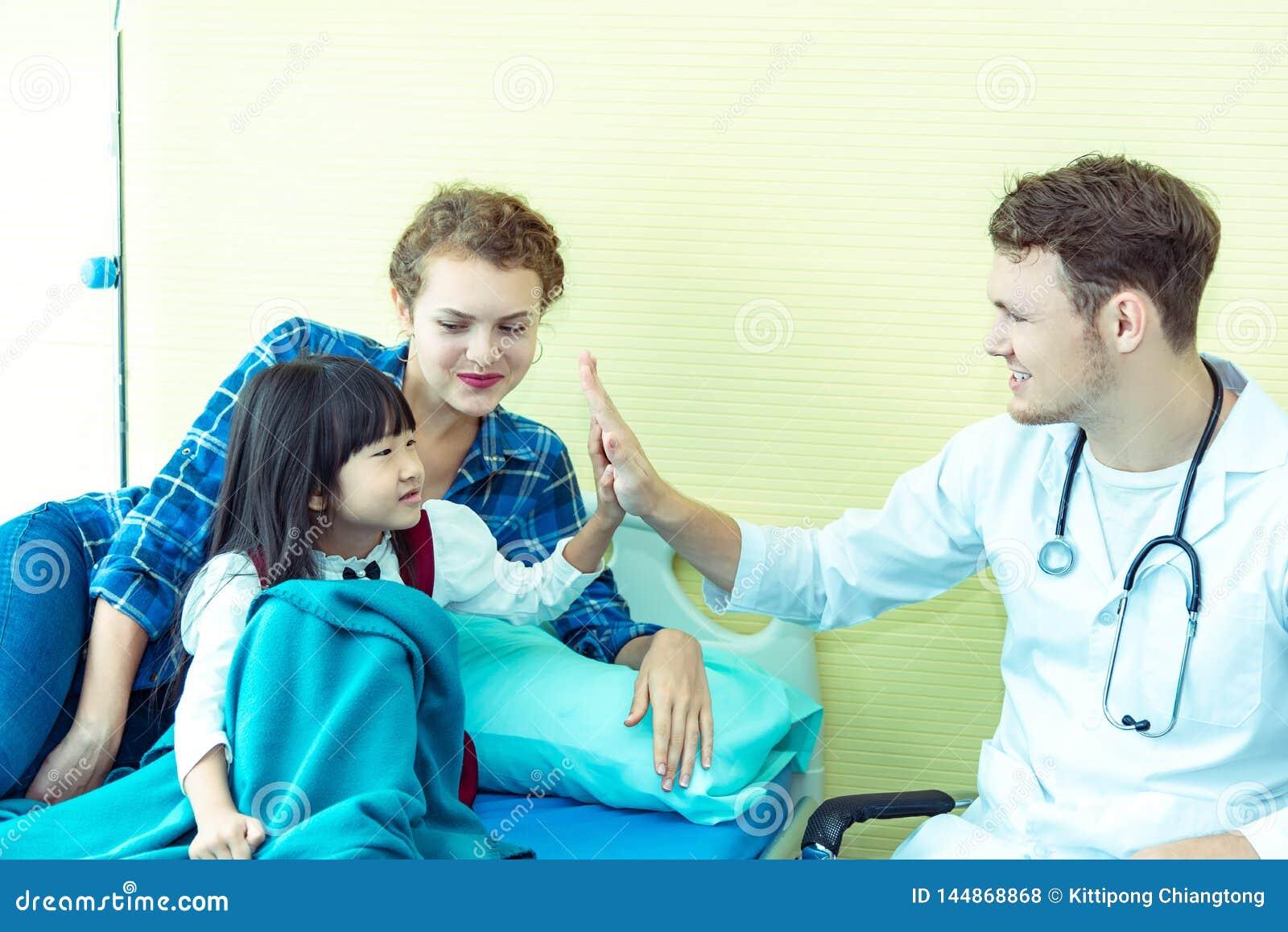 Młoda życzliwa caucasian pediatra samiec lekarka egzamininuje dziecko cierpliwej dziewczyny z jej matką na łóżku w szpitalu