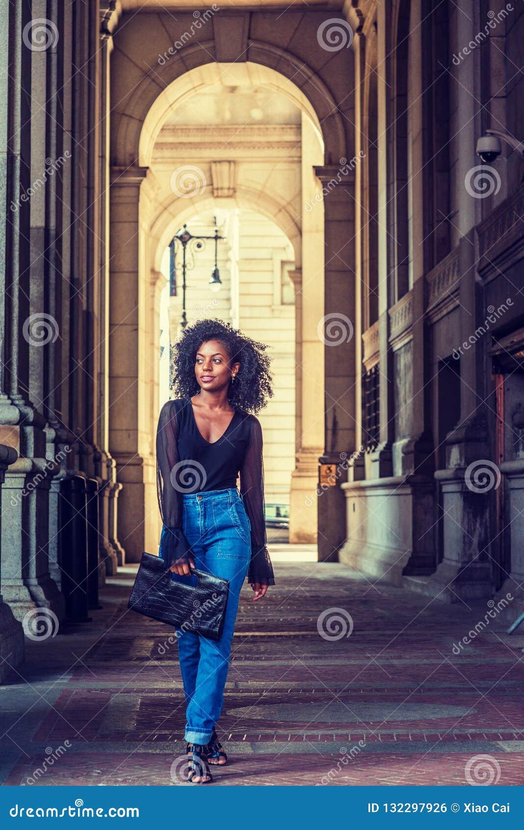 Młoda amerykanin afrykańskiego pochodzenia kobieta podróżuje, chodzący na ulicie w Nowym