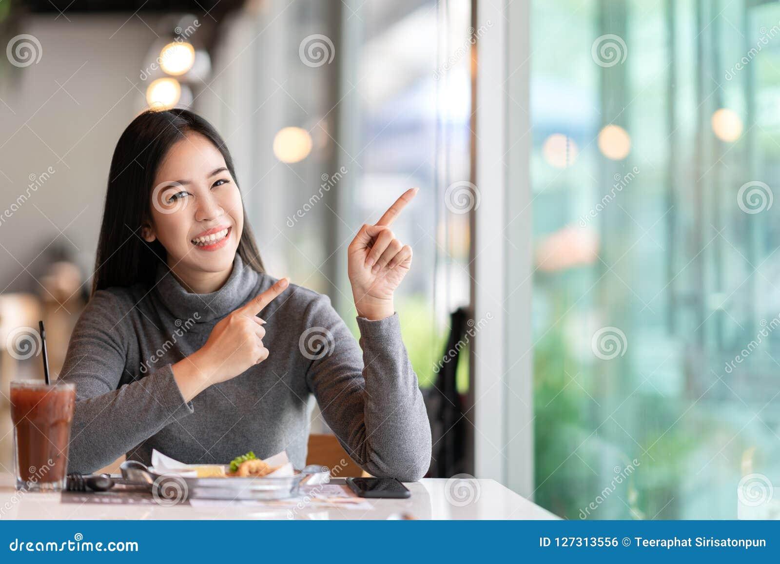 Młoda atrakcyjna azjatykcia kobieta wskazuje do strony czuje szczęśliwego zadziwiającego przy kawiarnią dla pokazywać wiadomość