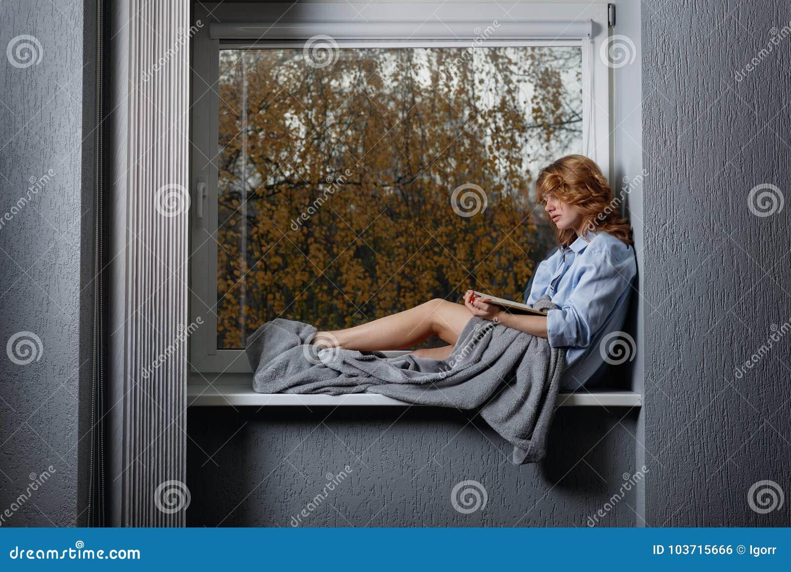 Młoda atrakcyjna dziewczyna na nadokiennym parapecie