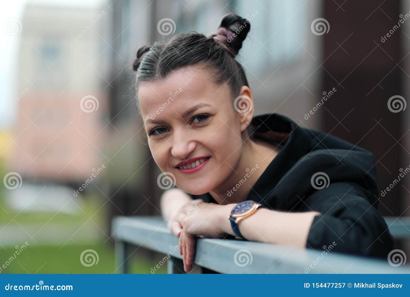 Młoda atrakcyjna kobieta w czarny kurtki i niebieskich dżinsów pozować plenerowy przeciw tłu budynek