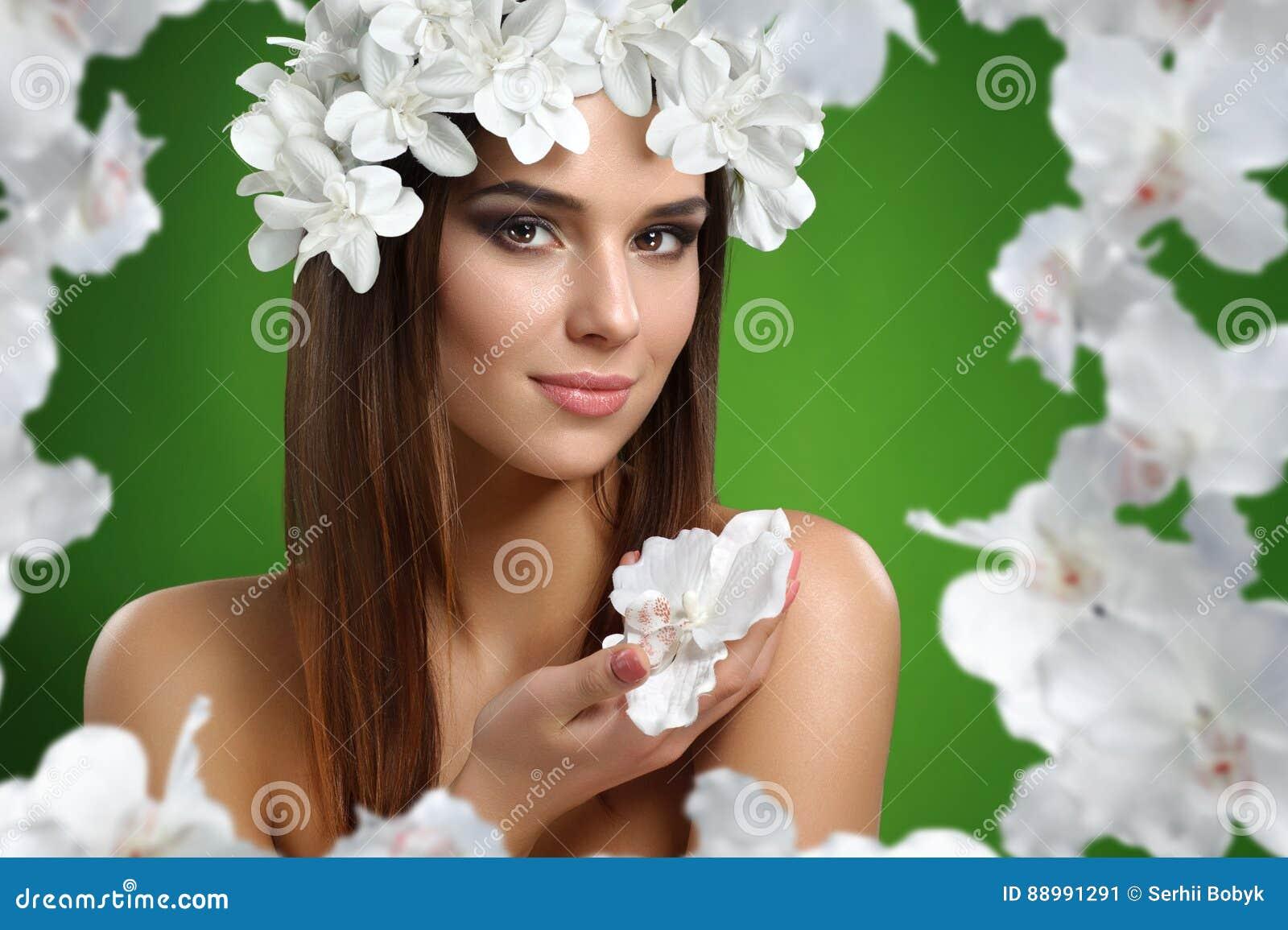 Młoda atrakcyjna kobieta z kwiatami w jej włosy pozuje w studiu