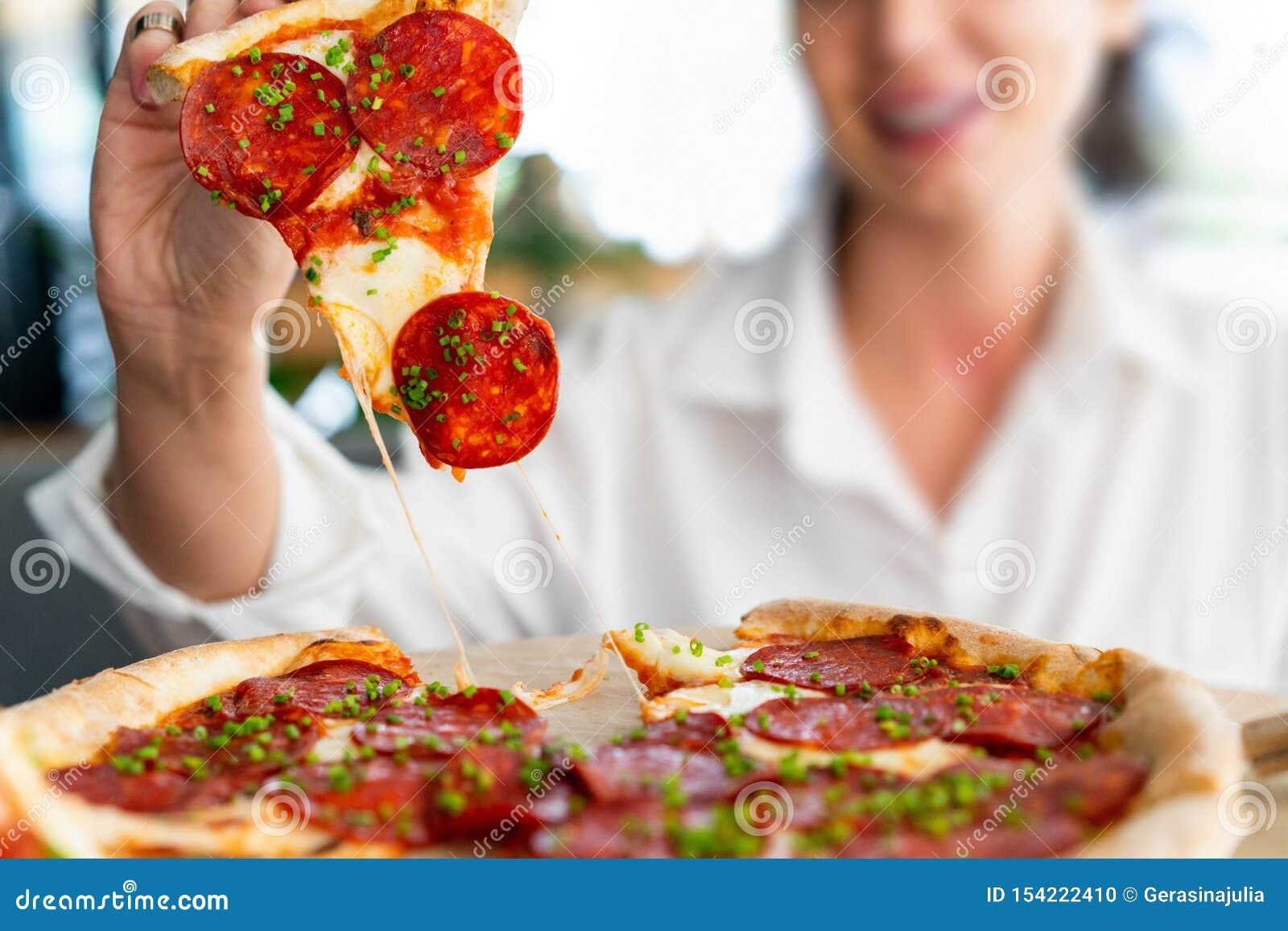 Młoda atrakcyjna uśmiechnięta kobiety łasowania pizza przy uliczną kawiarnią Nabranie posi?ek Nabranie dzień