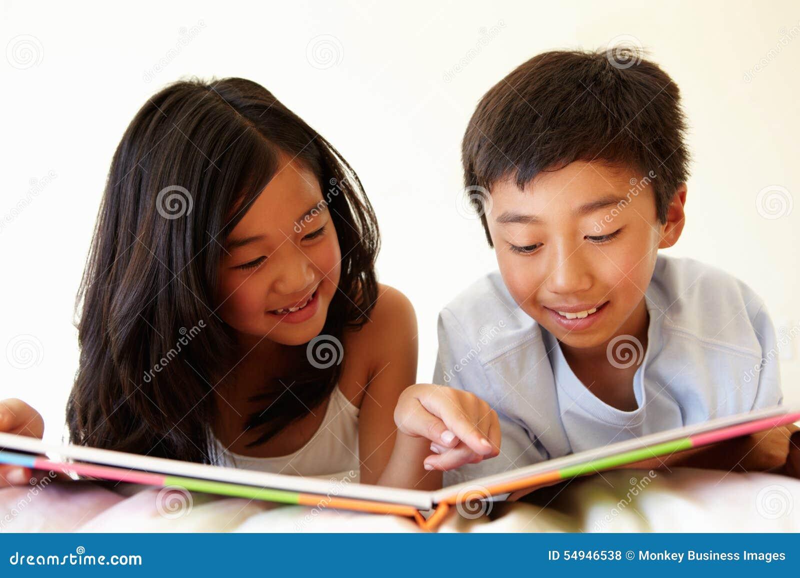 Młoda Azjatycka dziewczyny i chłopiec czytelnicza książka