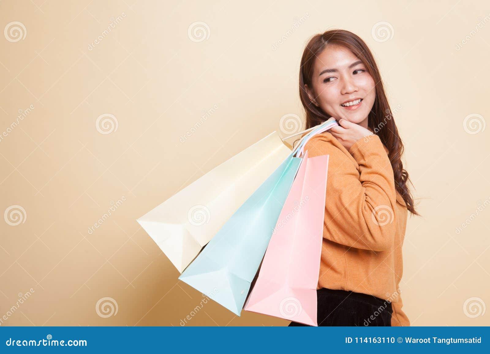 Młoda Azjatycka kobieta szczęśliwa z torba na zakupy