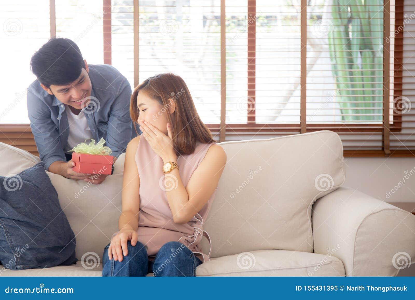 Młoda azjatykcia para świętuje urodziny wpólnie, Asia mężczyzna daje prezenta pudełku teraźniejszemu dla niespodzianki przy żywym