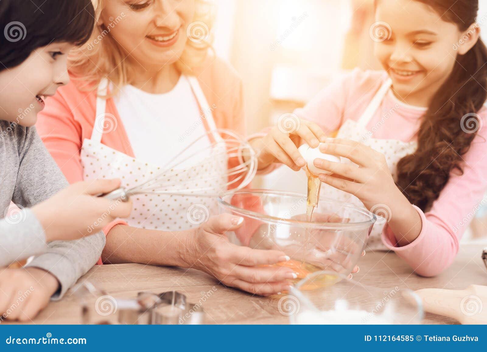 Młoda Babcia I Wnuki łamamy Jajka W Puchar W Kuchni Llittle