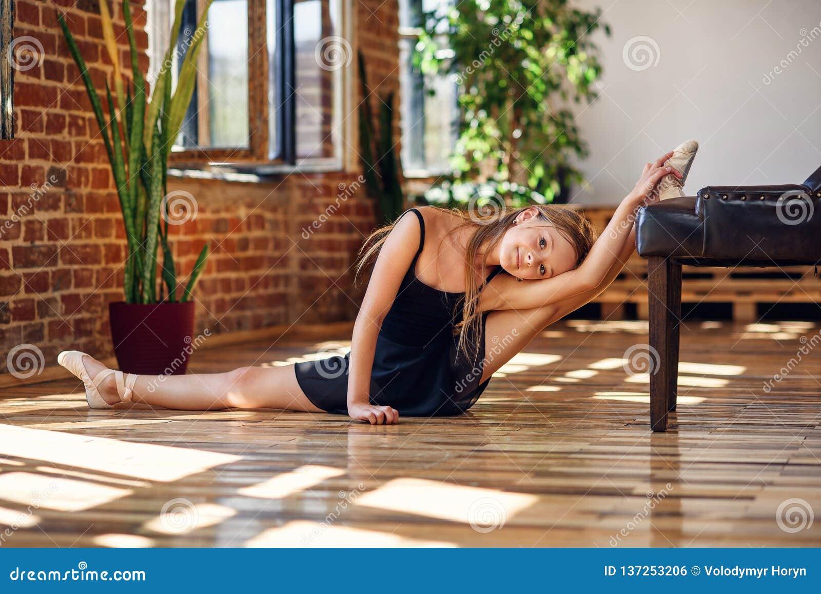 Młoda balerina robi dratwie w dancingowej sali