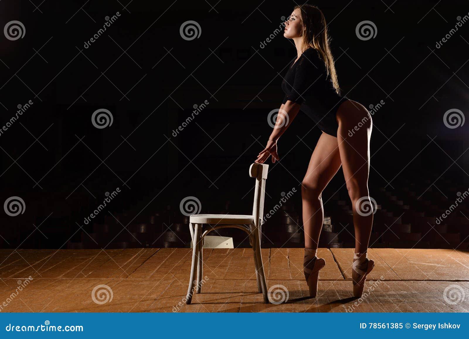 Młoda balerina w teatrze pozuje, w kostiumu, tanczy
